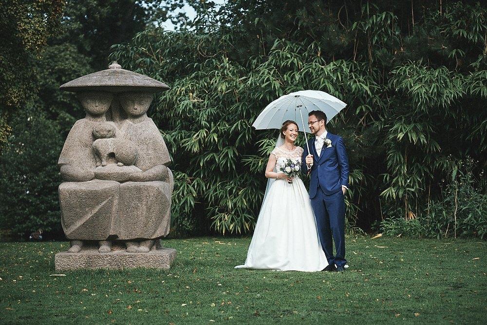 trouwshoot bruidsfotografie met paraplu in het park bij een beeld