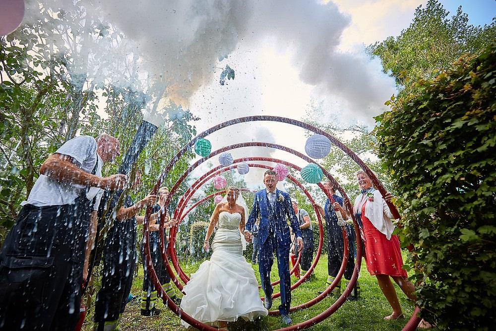 bruidsfoto als bruidspaar door een haag loopt van de brandweer