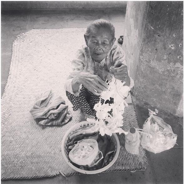 Veille dame vendeuse de collier de fleurs, à l'entrée d'un temple Birman, en été.
