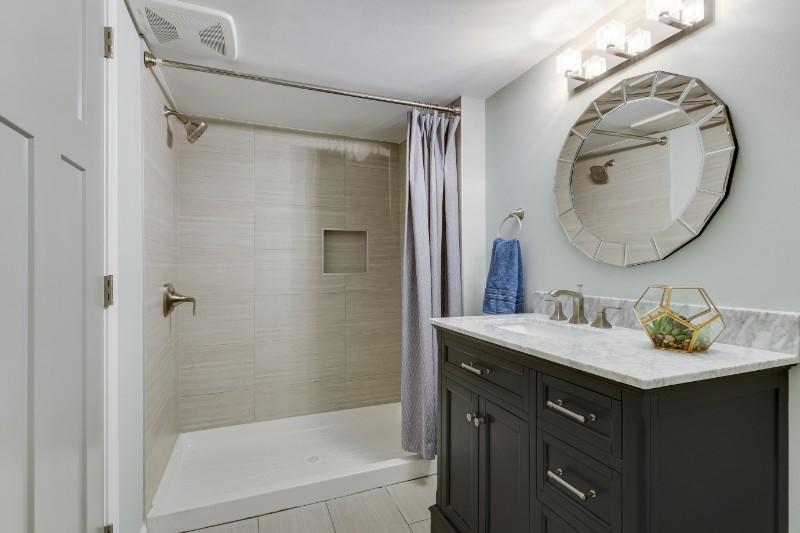 Tiffany Hanken   Interior Design   brings simple luxury to this bathroom with a black counter.