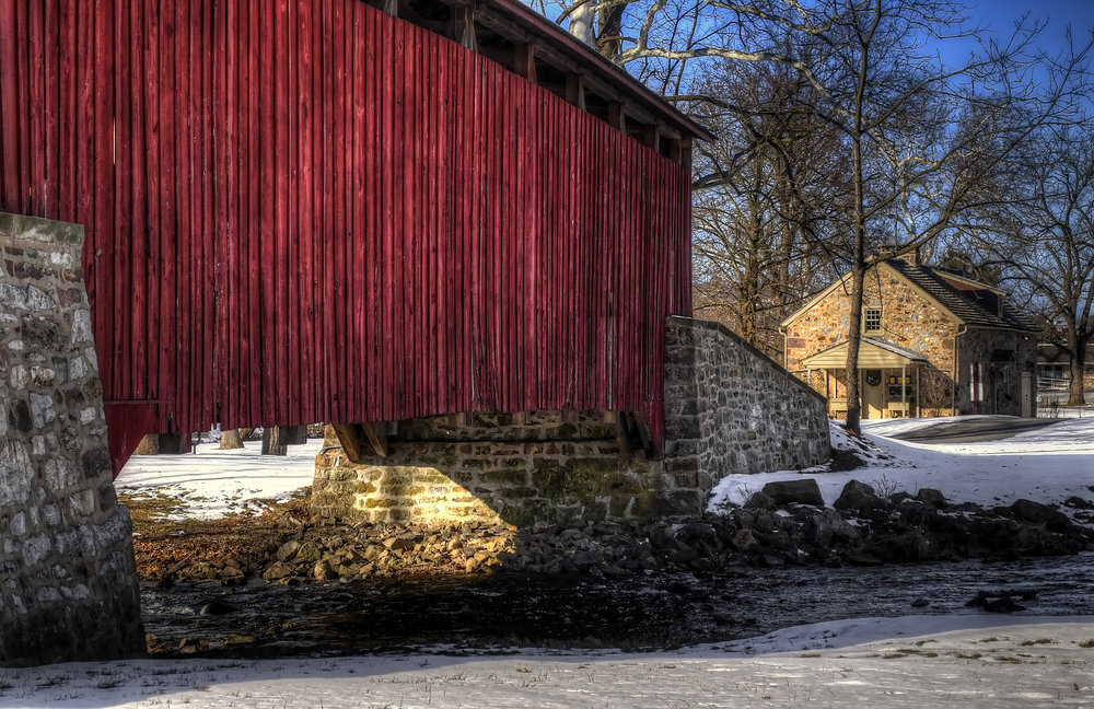 Winter view of the Covered Bridge and one of the Brownstones at Historic Poole Forge.