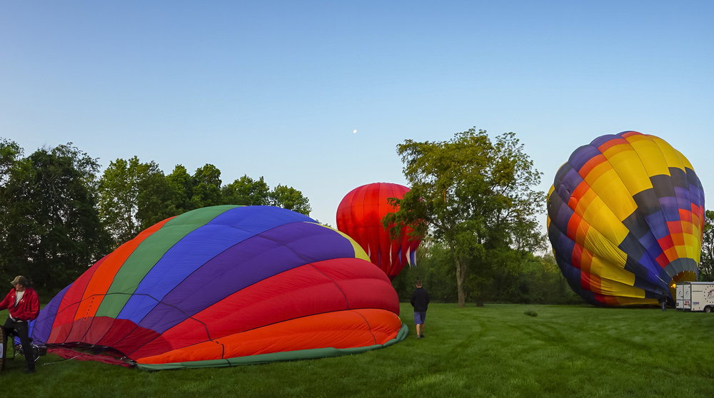 A panoramic view as the team prepares the balloons and the moon approaches the horizon to the west.