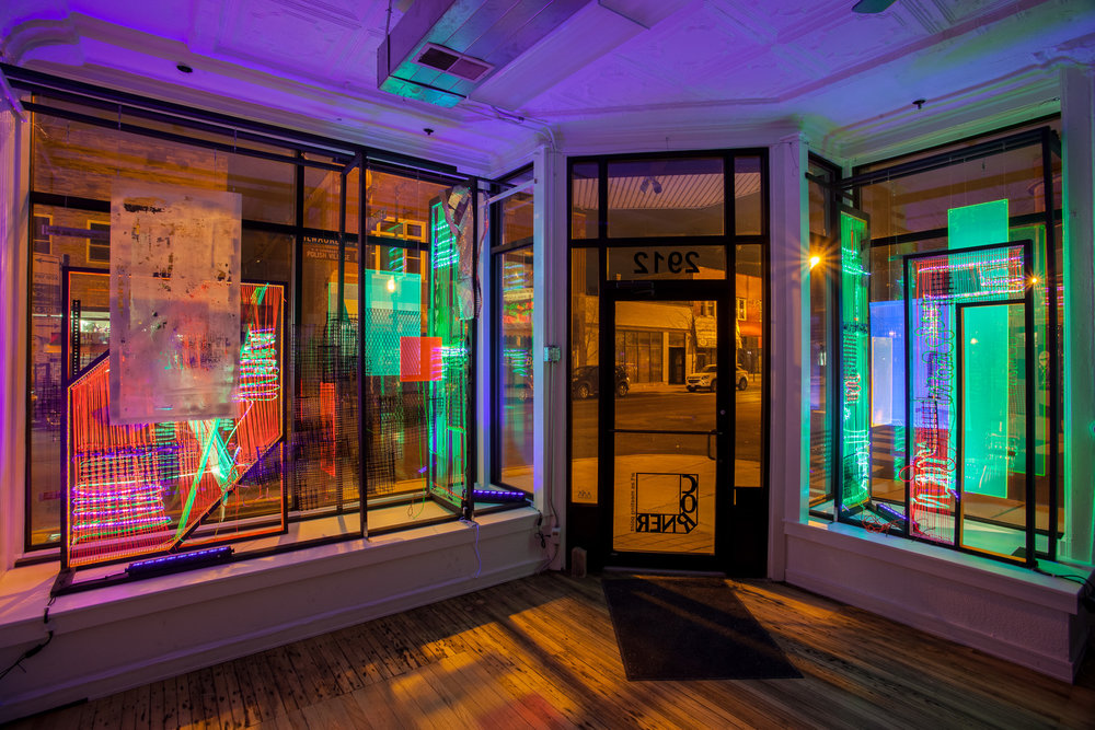 Mara Baker,  Chameleon Blind (Winter Light),  2018 ,  black light, rope, mason twine, plastic fencing, egg crate light grids, spray paint plexiglass and other found residues on constructed wooden frame. Site-specific installation in the storefront windows at Corner Project, Chicago, IL.