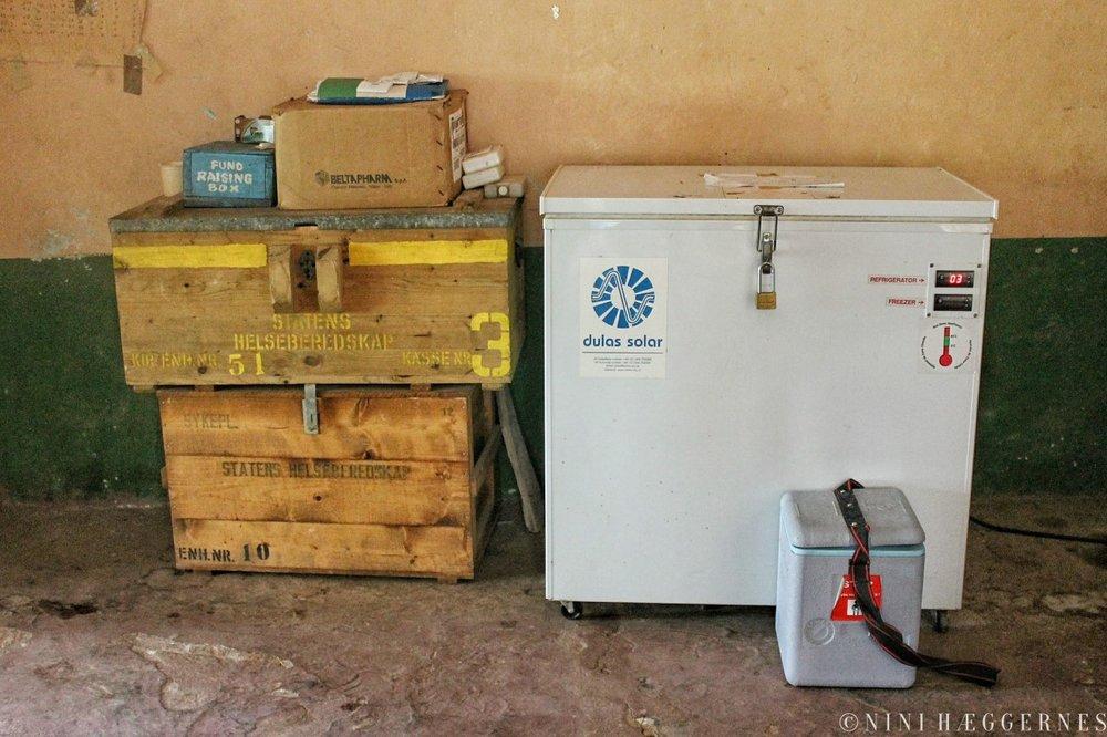 Foto Nini Hæggernes. En fund raising boks, kasser med utstyr donert fra Norge og en kjøl- og fryseboks drevet av et solcellepanel.