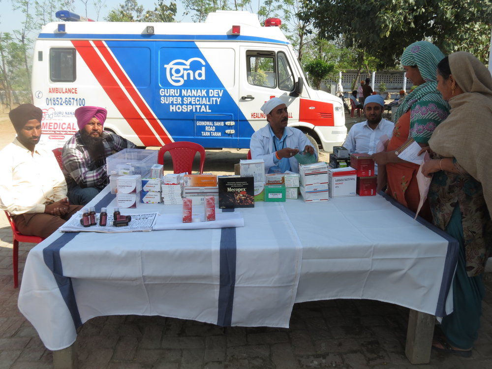 Medical camp team at pharmacy station with hospital ambulance in the background.