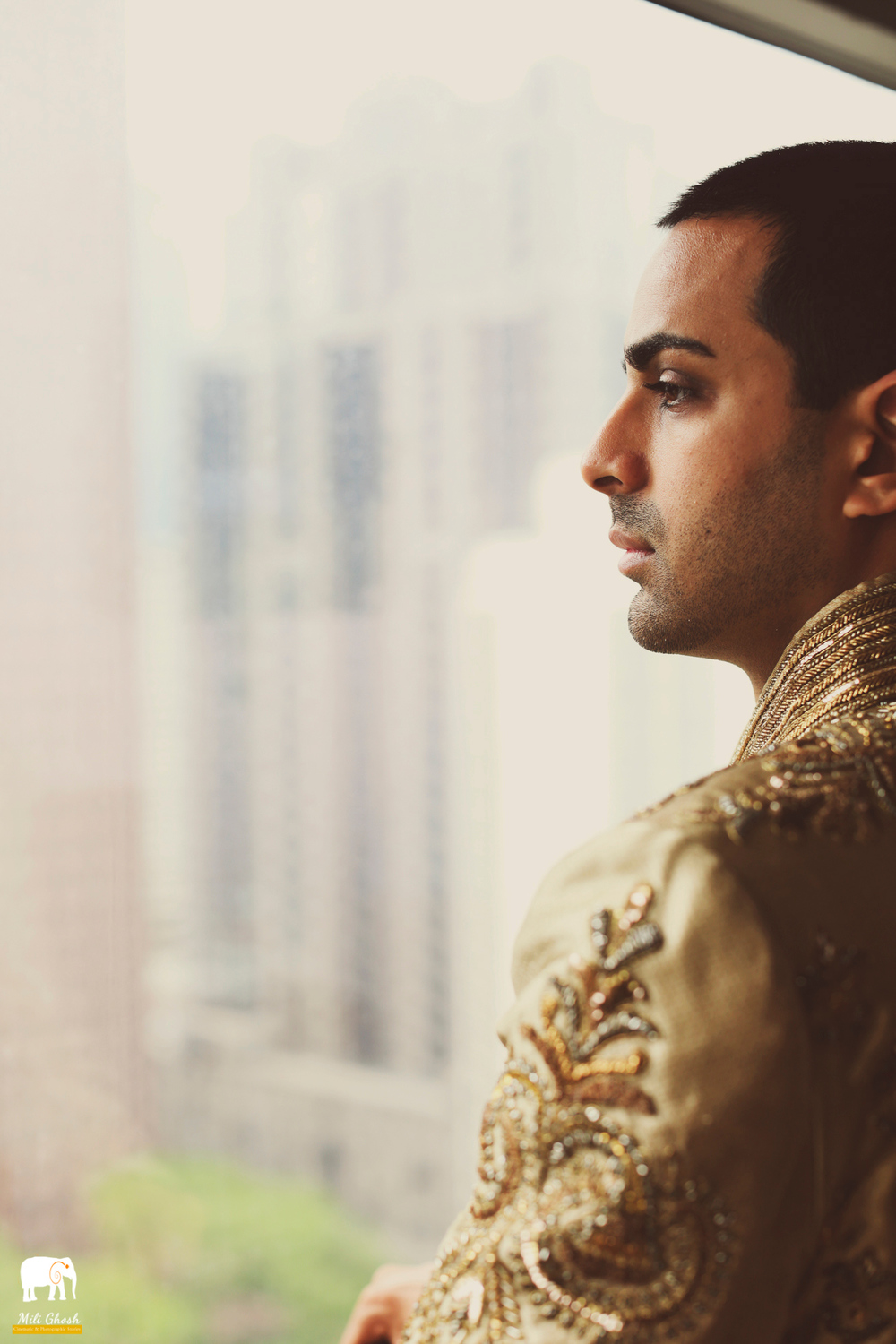 HANDSOME INDIAN GROOM LOOKING OUT WINDOW
