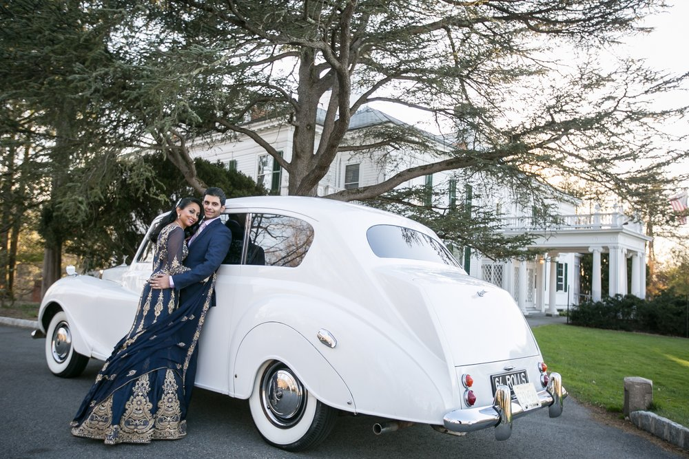 BRIDE AND GROOM ON VINTAGE CAR