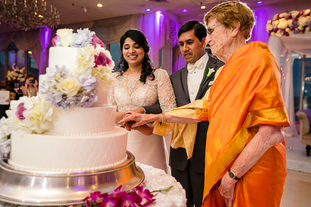 INDIAN WEDDING BRIDE AND GROOM CUT CAKE WITH FAMILY.jpg