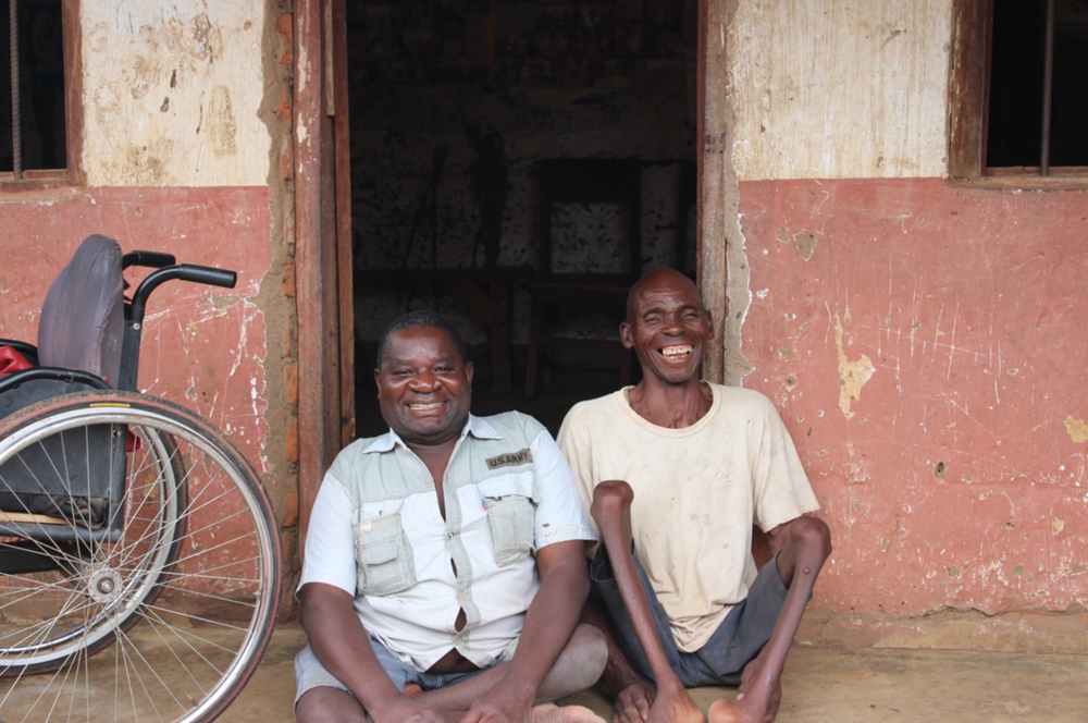 Luka (left) sits with his colleague, James Mulanje, a board member of the Association of People with Disabilities in Phalombe