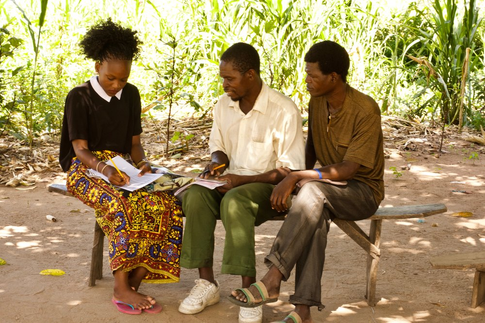 Fortunate, a Malaria Control Unit (MCU) worker, speaks with the Village Headmen of Mofolo village in Traditional Authority Nkaya, Balaka.  With support from the Village Headmen, the MCU's net distribution work begins with a registration survey. This maps households and numbers required in the distribution process.