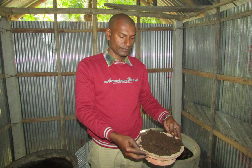 A local farmer takes a sample of vermicompost for harvesting.