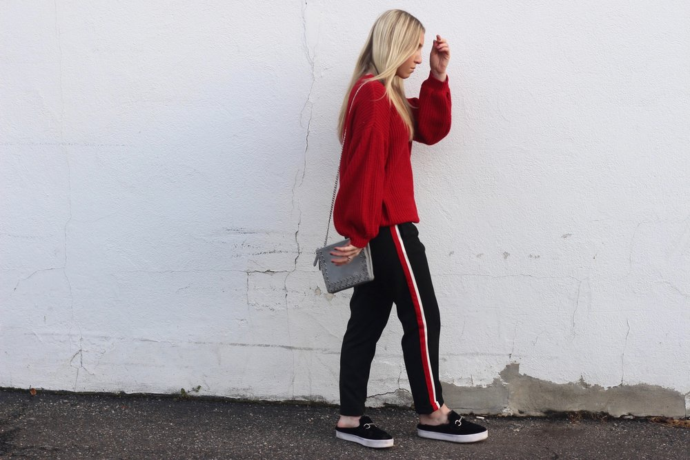 Carly of Au Courant Life in striped trousers, red sweater, and black slides