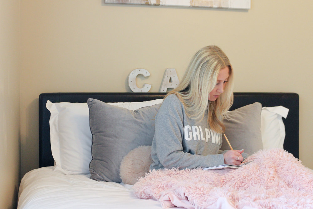 girl on bed with mug writing in journal bedtime routine