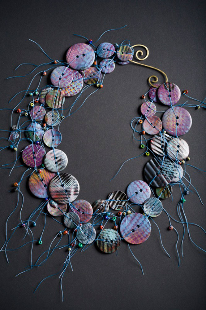 Hand-painted knotted button necklace with a hammered metal clasp.