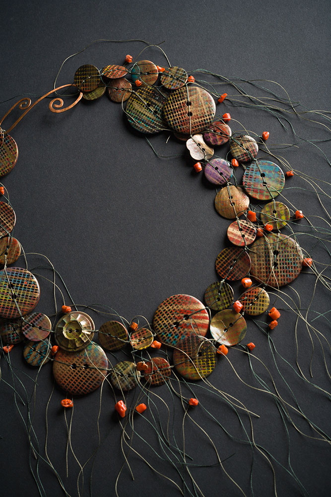 Hand-painted button necklace with hammered metal clasp.