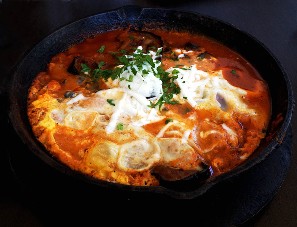 Shakshuka sizzles in a skillet.  Photo by and © Vision Studio