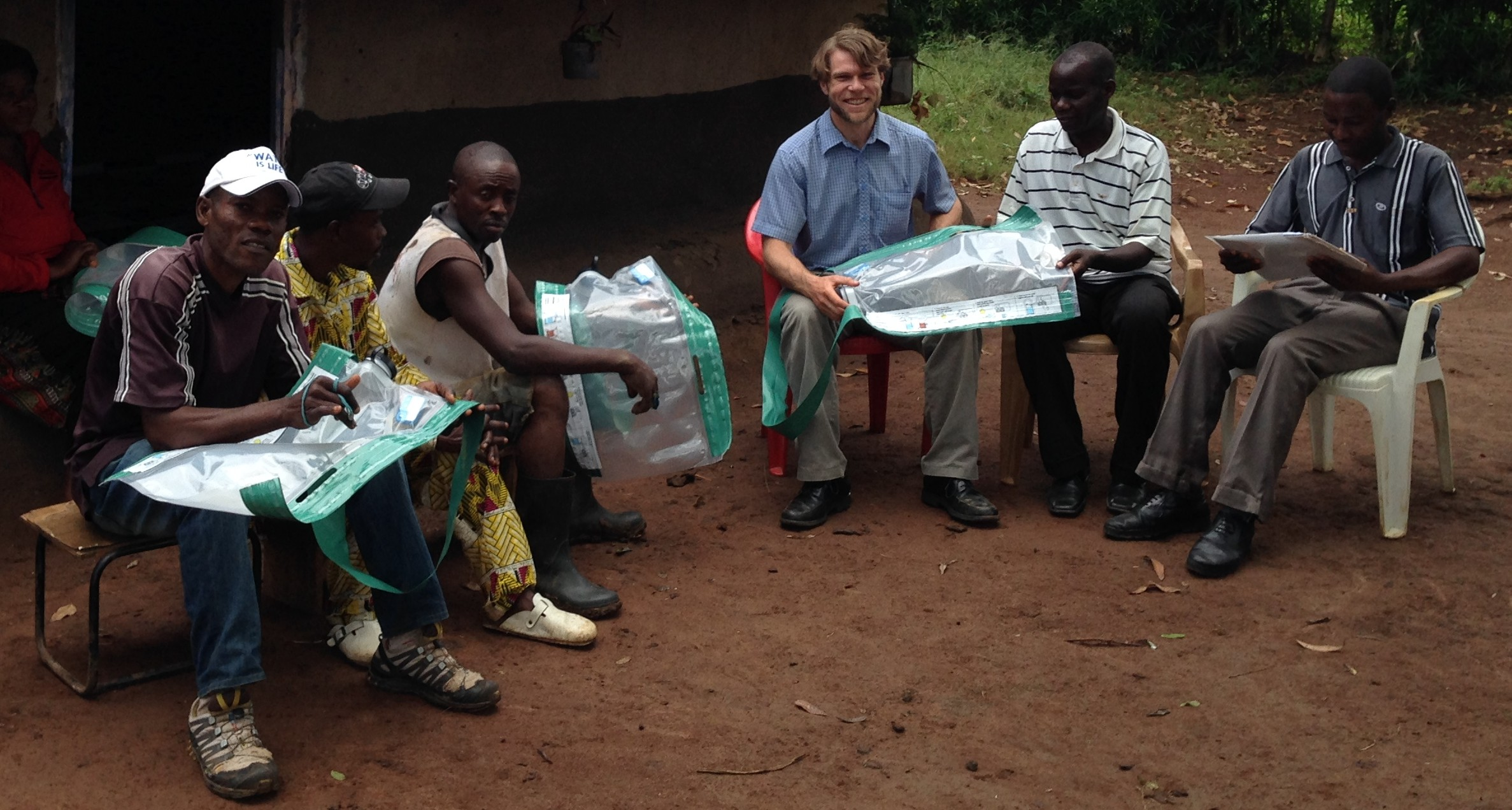 Charlie teaching a small group in Kyangwali Refugee Settlement how to use Smart Solar Purifiers.