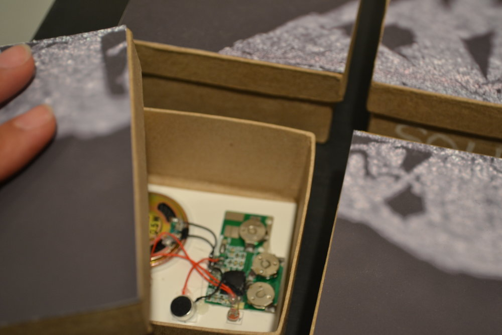 Open Auction   A collection of six handmade sound boxes, each containing a sonic burst of callings by legendary auctioneer John Korrey. Lift the lid and the light-activated board is tripped to amplify the recording. Playful exploration of another kind of vanishing physical retail environment, the Auction House.