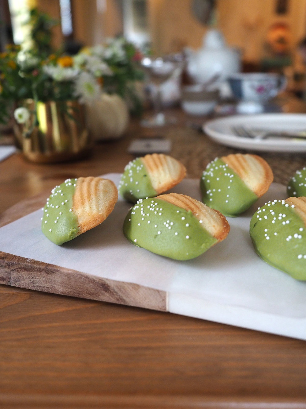 These delicious buttery madeleines are dipped in white chocolate and matcha green tea powder for a tasty tea party dessert! Just 4 ingredients and this recipe could not be easier. And while they have that classic matcha flavor, it isn't overwhelming — great for matcha and non-matcha fans alike.