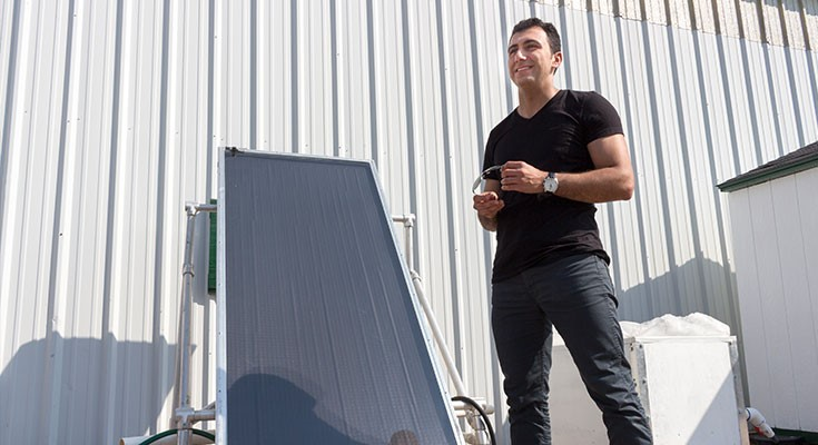 Photo courtesy of MSU Sustainability. Sina Jahangiri, PhD candidate and solar water heater researcher from MSU's Department of Mechanical Engineering, posing near a flat plate collector system for solar water heating.
