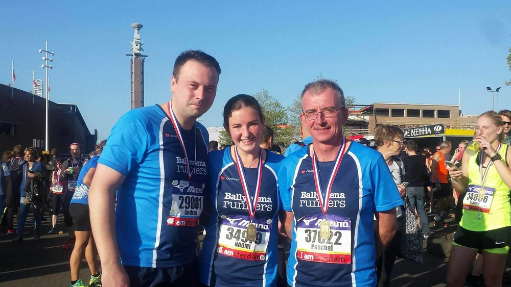 Andrew Hutchinson, Naomi Hutchinson and Paschal O'Sullivan proudly display their Amsterdam Half Marathon medals