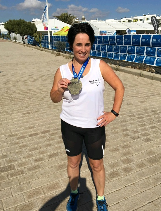 Claire Martin proudly displays her Lanzarote Marathon medal