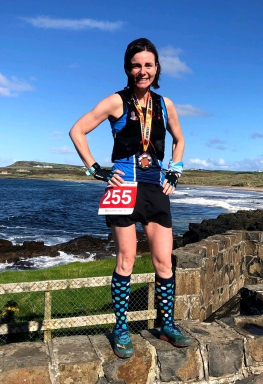 Vicki Dunn with the stunning scenery of the Causeway Coast Marathon as a backdrop