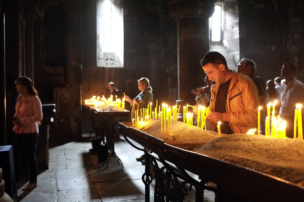 Lighting church candles in Armenia