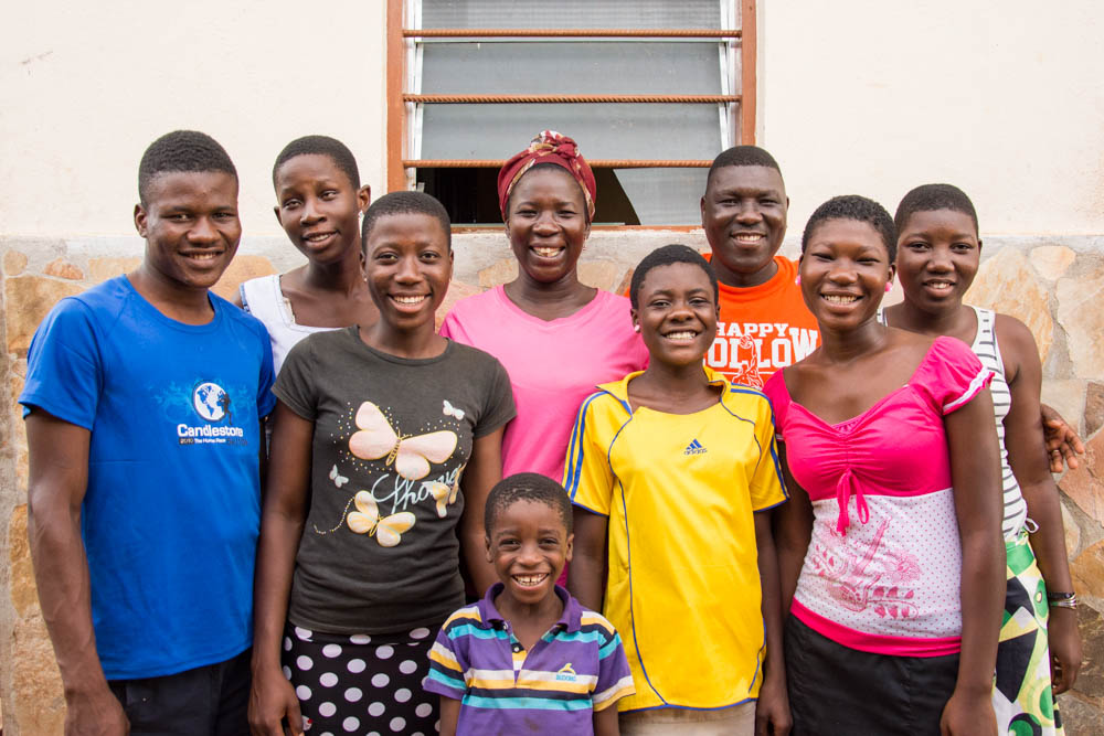 Boniface (orange shirt) and Abra (pink shirt, center) with their own 3 children and 4 of the other 8 children they have taken in as their own.