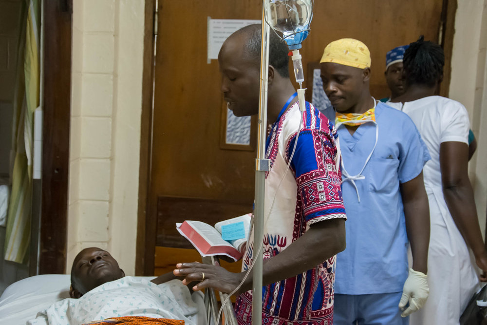 Jeremie prays with a patient as he is prepped for surgery at Hôpital Baptiste Biblique.