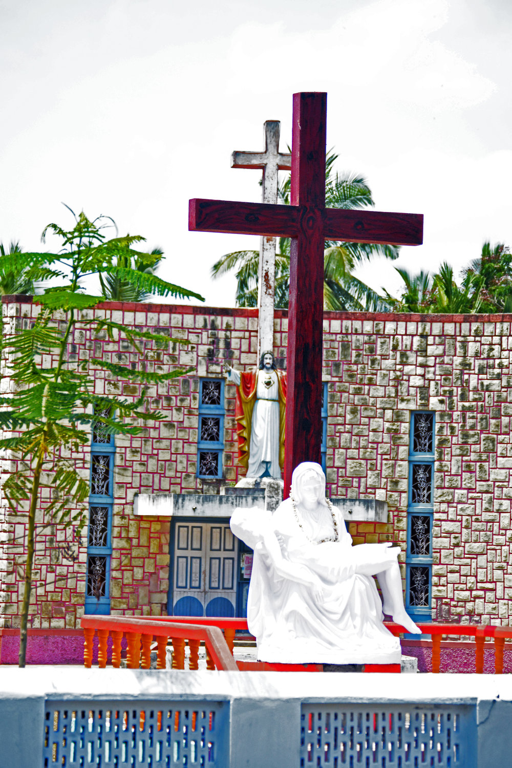 This statue is seen from the roadside outside of this church building in southern India.