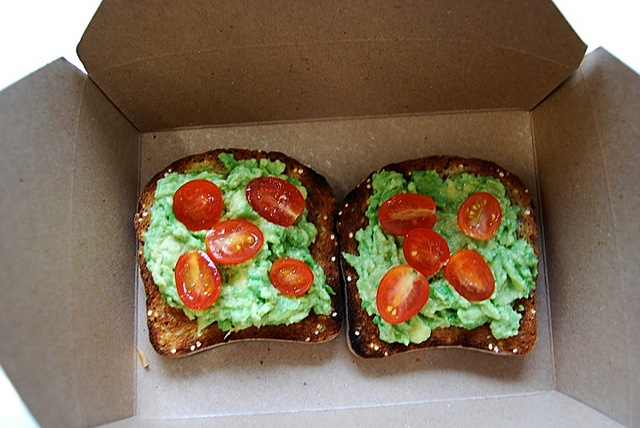 Gluten-free Breakfast toast, topped with avocados, baby tomatoes and sea salt