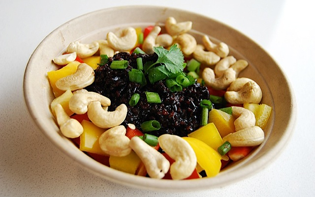 Forbidden Rice Bowl black beans topped with red and yellow bell pepper, cashews, green onions,  and cilantro, tossed in a tamari-lime dressing