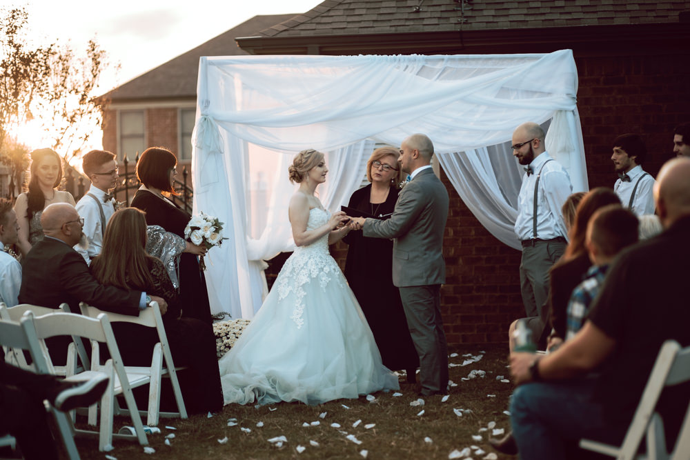 bride exchange rings sunset backyard wedding
