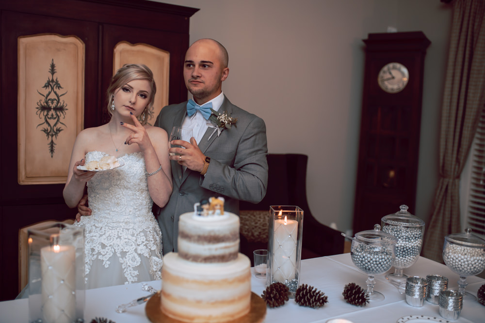 bride and groom tough pose by cake