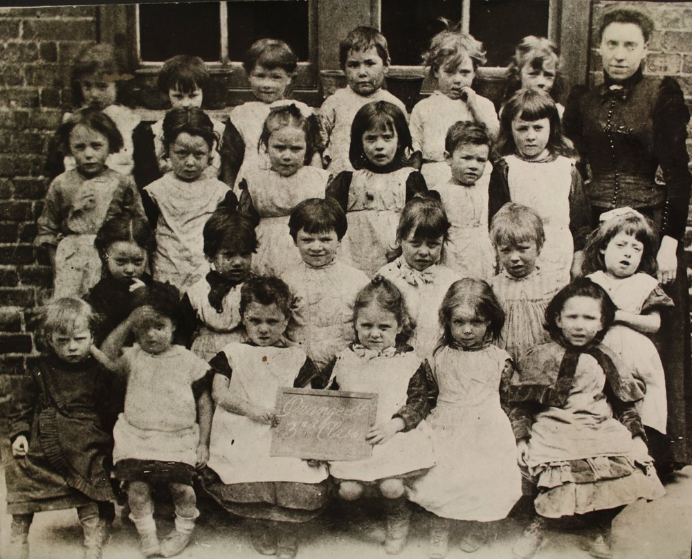 The Infant Class of Orange Street School (now Jerwood Space in Borough) squinting in the glaring sun in the 1890s. One of the ways we can tell this is an Infants Class is because all the children are wearing smocks. In the 19th Century boys only started wearing trousers when they were 6 or 7 years old!