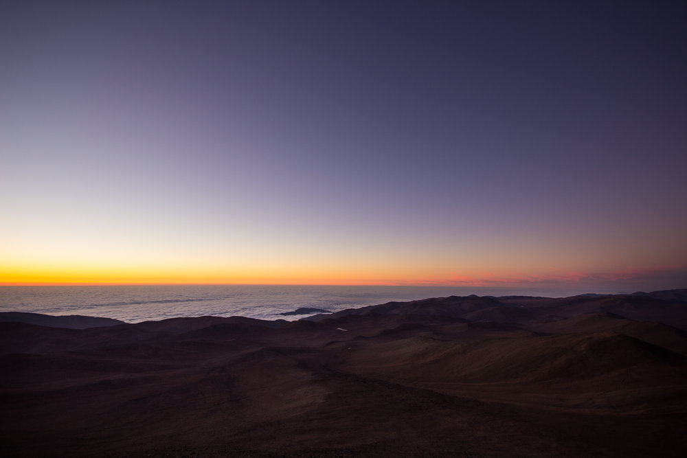 North, toward Antofagasta. The clouds, thousands of feet below, hide the Pacific Ocean. A low inversion layer, like that seen here, portends excellent seeing for the night. © Dr. Grant Tremblay