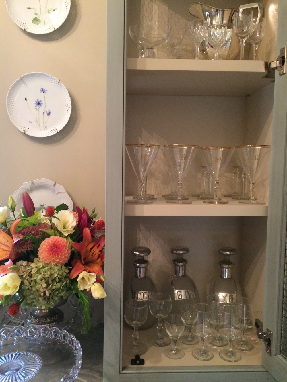 Stem and bar ware in cabinets and flowers in a vintage silver plate flower arrangers.