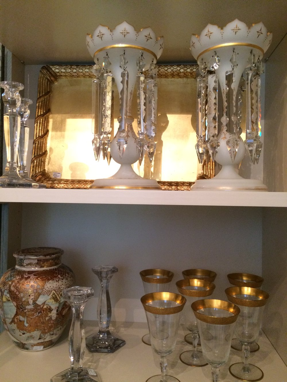 A close up of a cabinet full of lusters and stem ware.