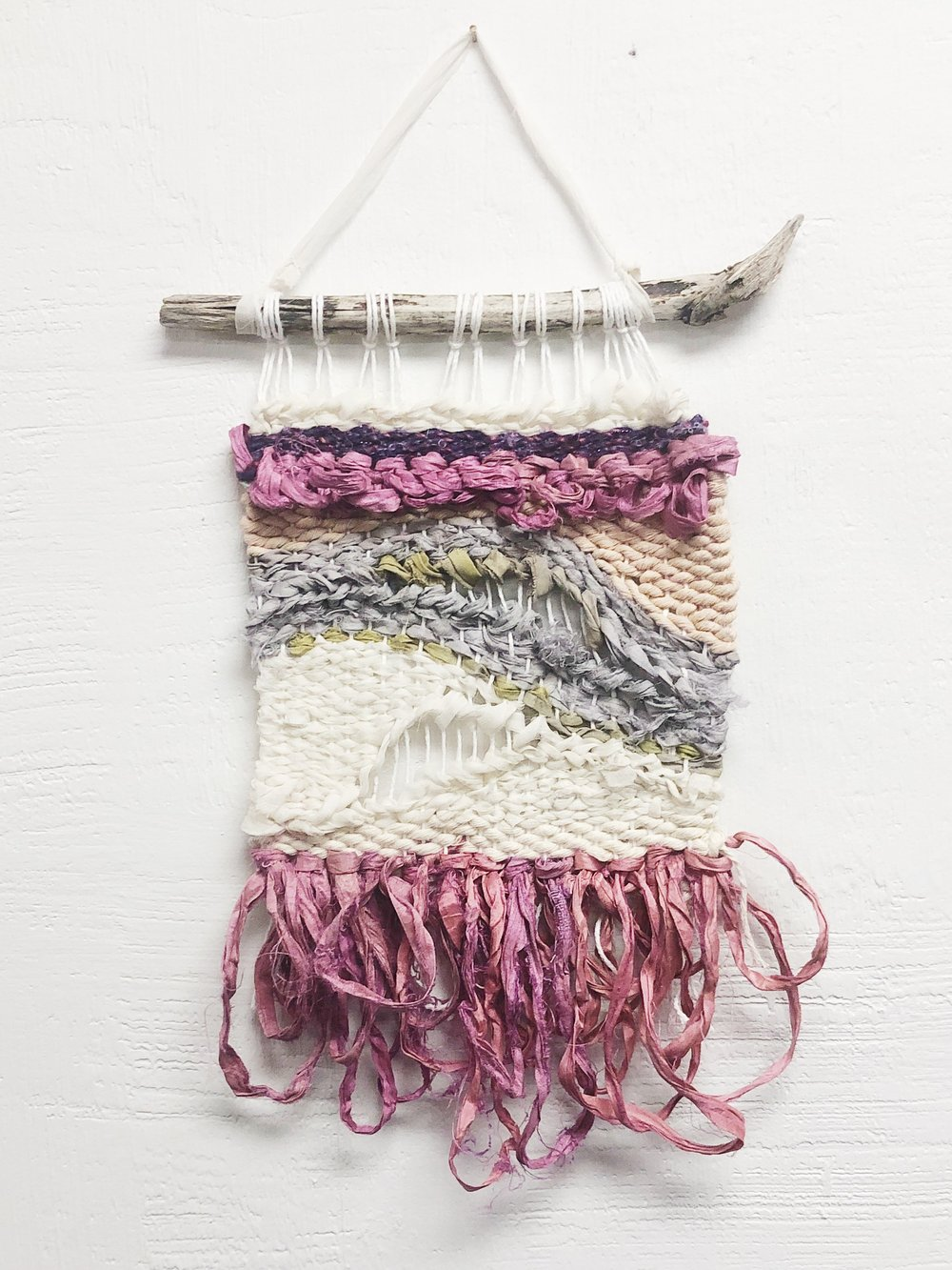 Blush Tone Negative Space Woven Wall Hanging $35  Look at this one-of-a-kind beauty, ready to fulfill the most bohemian space. This piece is a beautiful combination of naturally dyed cotton rope, upcycled saris, and a gorgeous purple yarn.