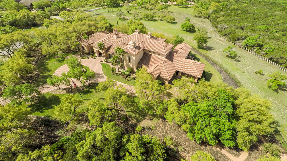 Gated elegant home features sprawling manicured grounds, expansive private Zen Gardens, circular driveway centered with three tier Old European Cantera Fountain