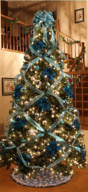 Color shemed trees can accenturate the colors in your existing decor. By either using some of the same colors or by using a contrasting color. This ribbon tree is very beautiful. The ribbon leads the eye around the tree. via:  Holidappy