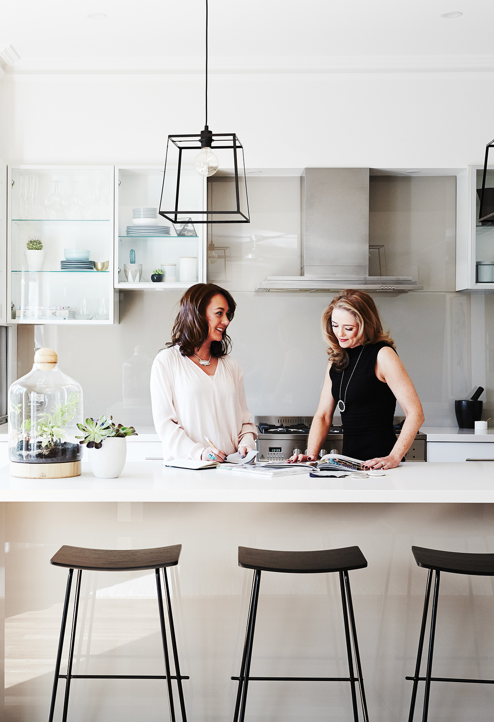 Designer Michelle Hart (left) pictured with client Georgina in the stunning, open kitchen. Bar stools from Relax House.