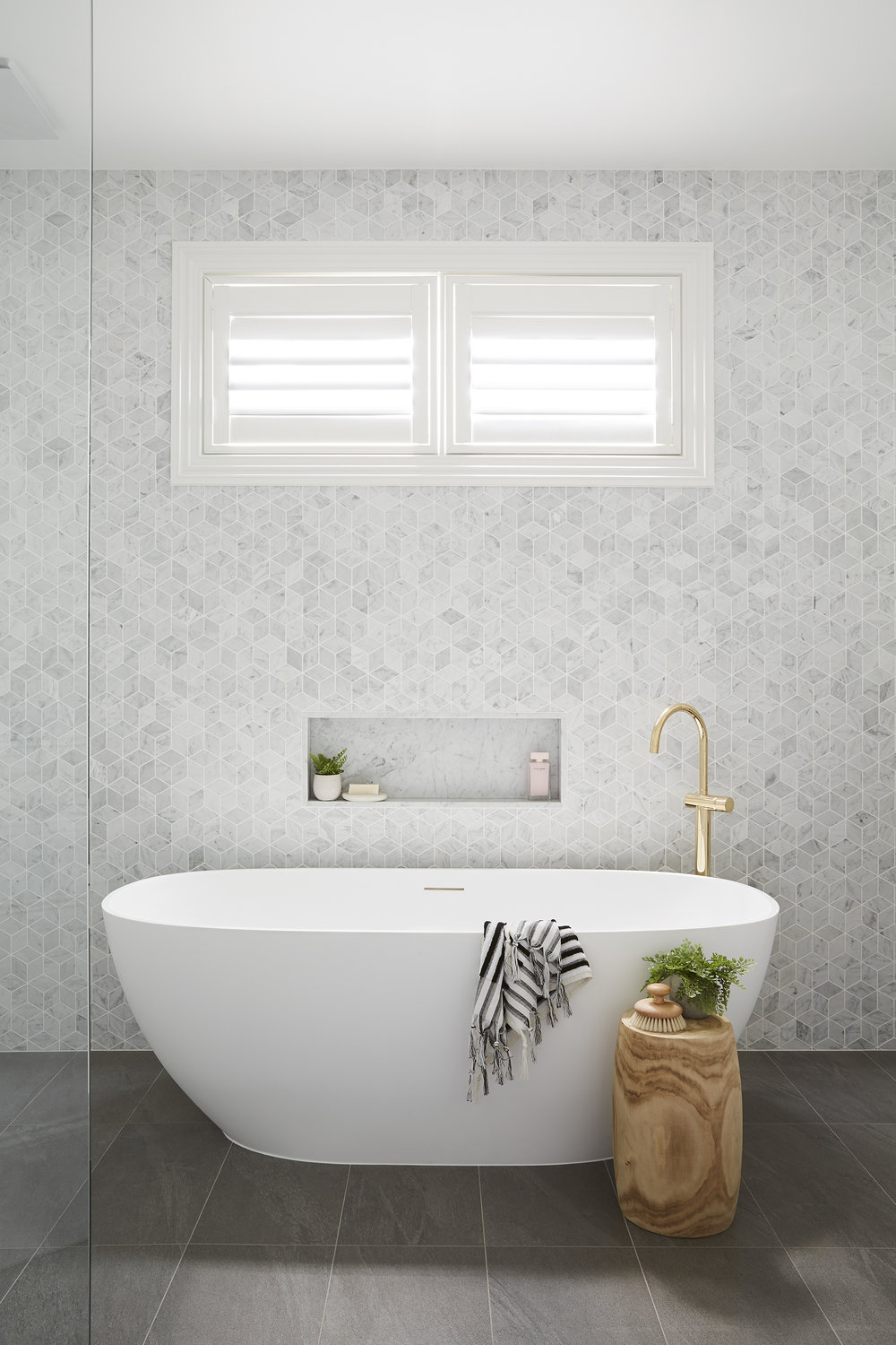 """These finishes are quite classic but we modernised them – for example, we've used marble tiles in more contemporary shapes,"" says Julia.  Tiles from Beaumont Tiles; plantation shutters from DIY Blinds; vanity, Sussex tapware and bath from Reece; towels from Loom Towels."