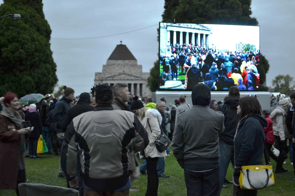 Attendees at the Dawn Service in Melbourne watch a big screen, 2015