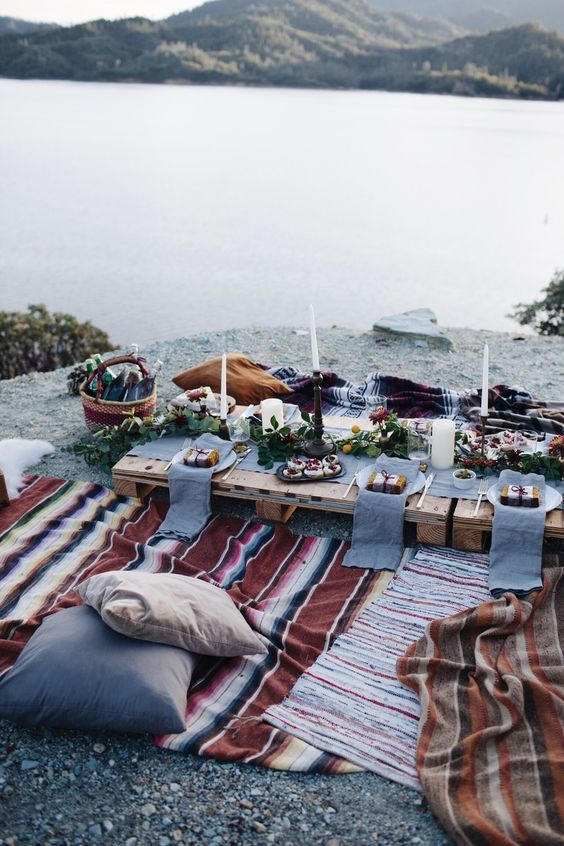 lake picnic with blankets and candles