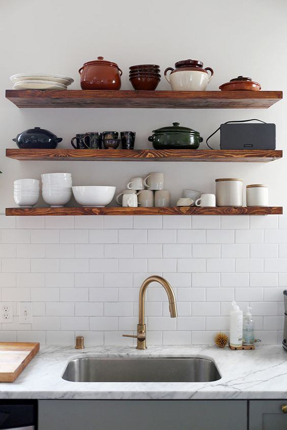 Wooden shelves with ceramic plates above kitchen sink