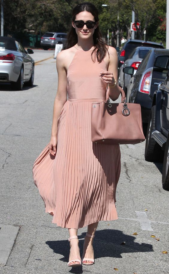 Emmy Rossum looking casual chic in a nude pink dress with matching heels and oversized leather bag.