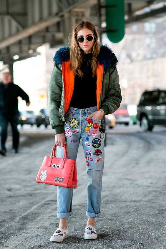 Chiara Ferragni perfectly styled in an oversized bomber jacket paired with faded embroidered denim jeans and matching handbag.