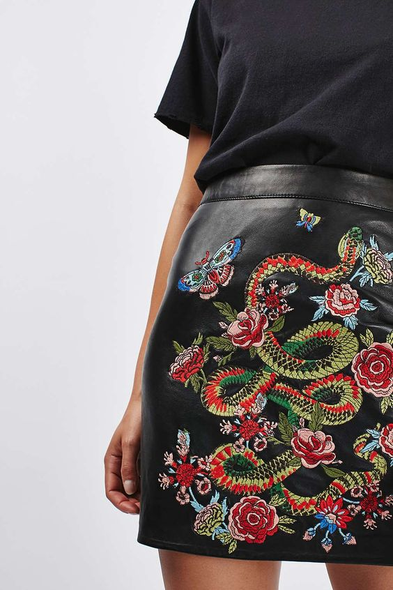 Intricate embroidered snake pattern on leather mini skirt
